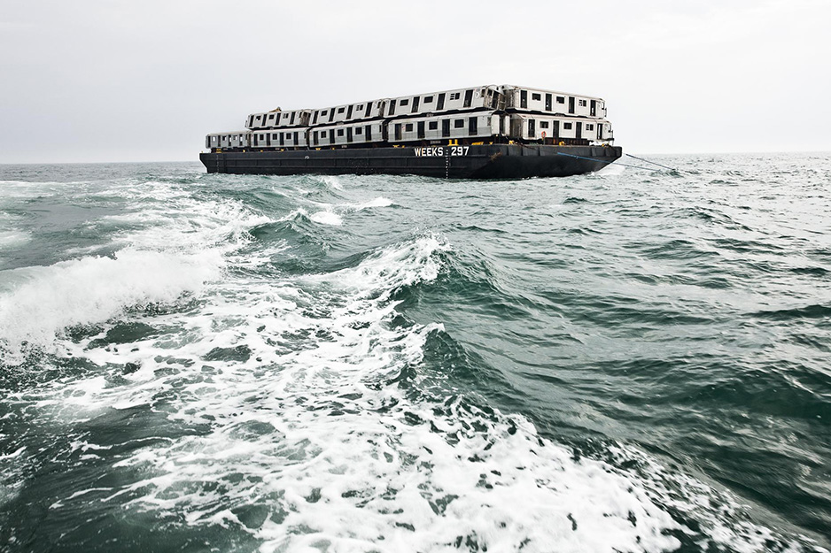 Subway cars piled on a barge and carried out to open seaVagones de metro apilados en una barcaza y transportados a mar abierto